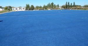 La cancha de hockey ya cuenta con su alfombra de cesped sintetico extendida en el terreno