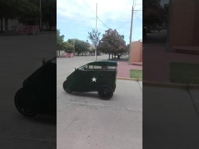 Un triciclo carrozado circula por las calles de la Ciudad